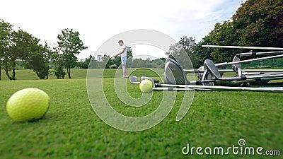 Spieler verwendet Golfclub, um Schläge auf einem Kurs zu üben stock video footage