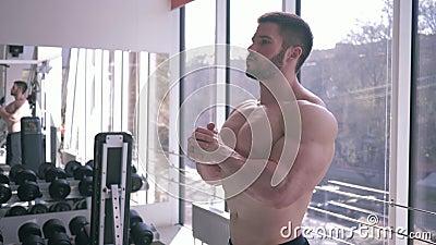 Spiersport mannelijke naakt-chested met atletisch lichaam warmt na sterkte opleiding in de bouw van spier in gymnastiek op stock video