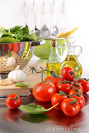 Spinach leaves in strainer with tomatoes