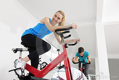 Spinning; women cycling at the gym