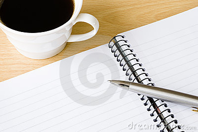 Spiral notebook with cup of coffee and ballpoint