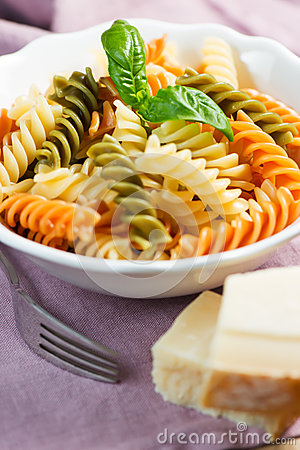 Spiral pasta with cheese and basil on table
