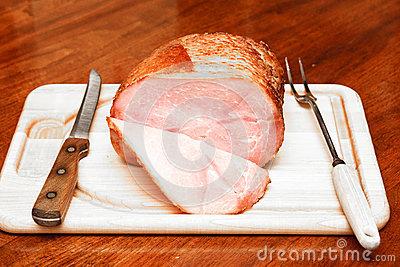 Spiral Sliced Ham on Cutting Board with Utensils