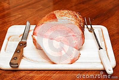 Spiral Sliced Ham on Cutting Board with Utensils