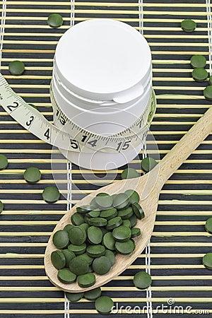 Free Spirulina,chlorella Pills And Measure Tape Around Pill Bottle Royalty Free Stock Photography - 84336577