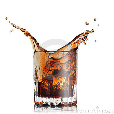 Splash of cola in glass with ice cubes