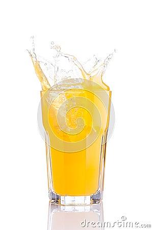 Splash in glass of orange soda with ice cubes
