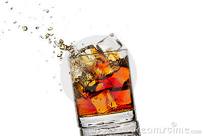 Splash in glass with whisky and ice cubes
