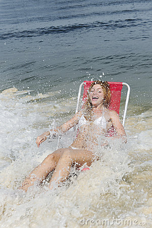 Splash: woman surprised by waves of the ocean