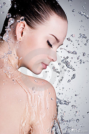 Splashes and drops of water around the female face