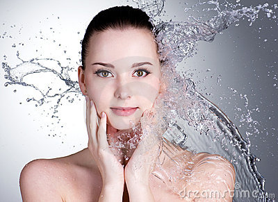 Splashes of water on face of beautiful woman