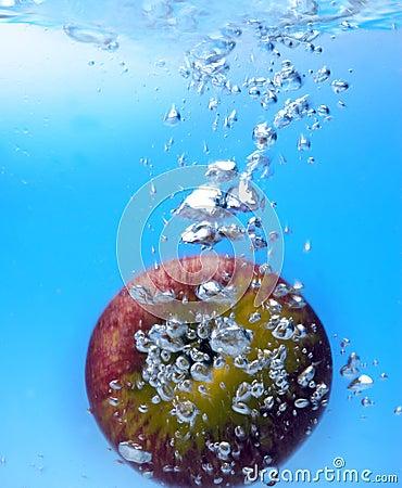 Splashing apple into a water