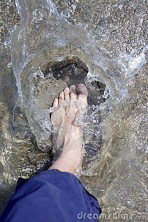 Splashing water tourist feet on beach shore