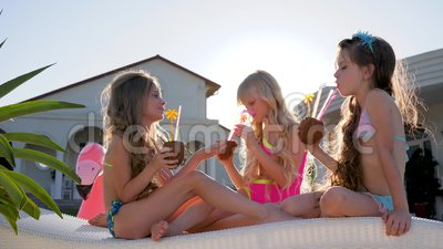 Spoiled Children With Colored Cocktails On Sun Lounger, Little Girls In Swimsuit Have Fun Near Villa In Backlight, Rich Stock Video - Video of happiness, smiling: 96839181