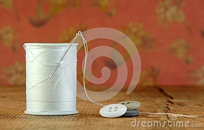 Spool of Blue Thread with a Needle and Buttons