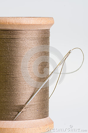 Spool of brown threas with a needle