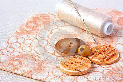 Spool of thread and buttons on a cloth