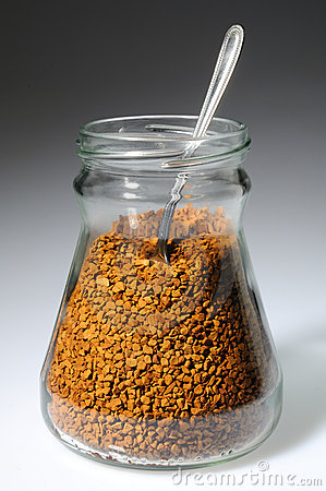 Spoon in glass bank with an instant granules coffe