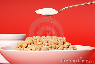A spoon sprinkling sugar on a bowl of oat cereal on red backgrou