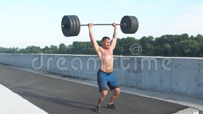 Sport, Bodybuilding, Lebensstil und Leutekonzept - junger Mann mit dem Dummkopf, der Muskeln in der Turnhalle biegt
