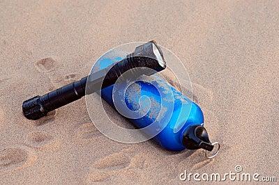 Sport bottle and flashlight in desert
