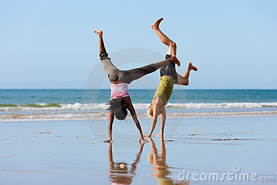 Sport couple doing gymnastics on the beach