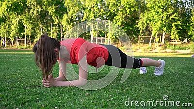 Sport dziewczyna robi desce ćwiczyć na gazonie zbiory