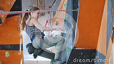 Sport estremo, bouldering Una giovane donna che scala, chiedente un aiuto e scendente archivi video