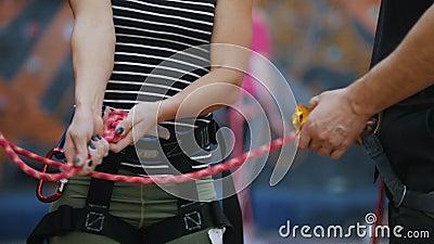 Sport estremo Una donna lega le corde della protezione per la scalata nell'ambito delle istruzioni della vettura video d archivio