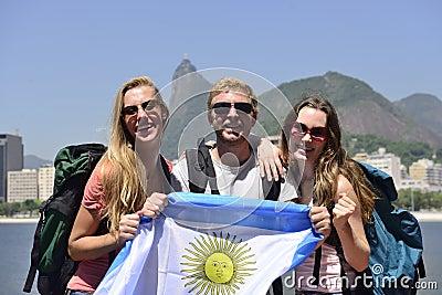 Sport fans friends in Rio de Janeiro holding Argentinian flag.