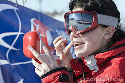 Sport girl snowboarder applying face pack outdoors