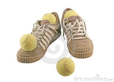 Sport shoes next to 4 tennis balls