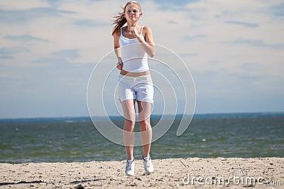 Sport woman running in sea coast