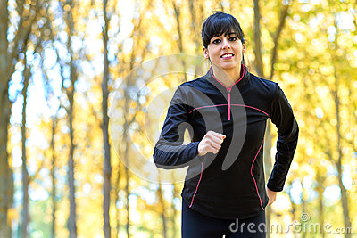 Sport woman running with trees on background