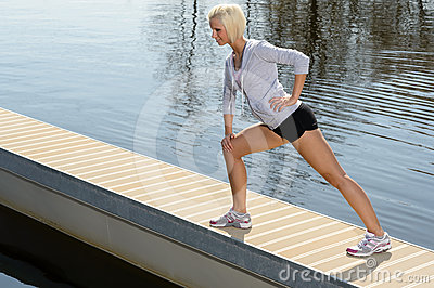 Sport woman stretch body on water pier