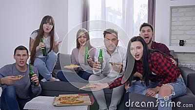Sportfreunde, die entscheidenden Moment des Spiels aufpassen und glückliches für den Sieg, der auf dem Sofa vor Fernsehen isst Pi
