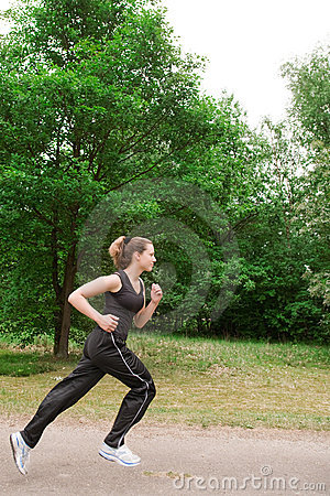 Sportieve jonge vrouw die over een meest forrest weg loopt