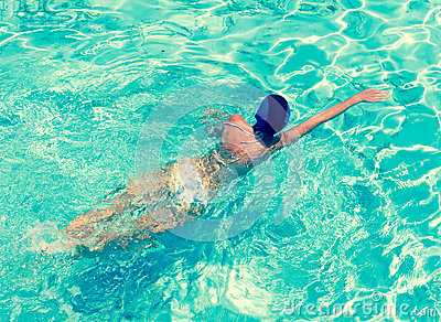 The sporting woman swims in bright blue water