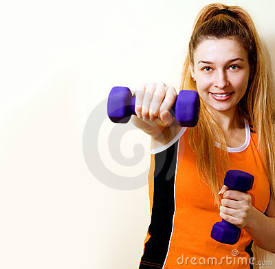 Sportive athletic woman working out with dumbbells