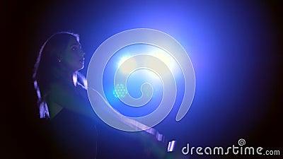 Sportive, beau, la jeune femme faisant la diverse force s'exerce avec des poids La nuit, à la lumière de multicolore clips vidéos