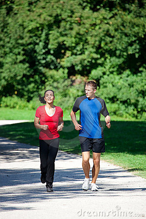 Sportive couple jogging together on summer day