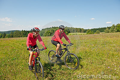 Sportive couple riding bike in summer meadow