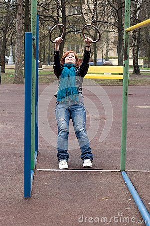 Sportive girl hanging on the rings
