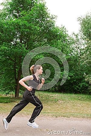 Sportive junge Frau, die über eine forrest Straße läuft