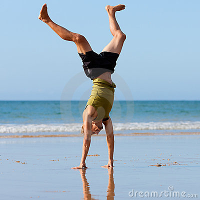 Sportive man doing gymnastics on the beach