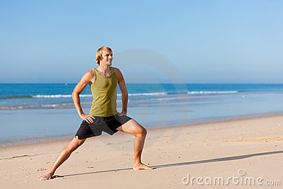 Sportive man doing gymnastics on the beach