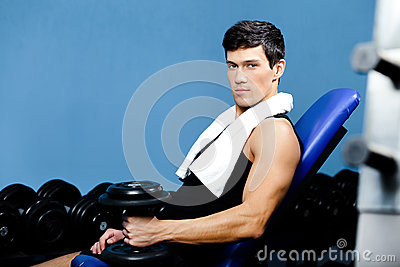 Sportive man rests holding a weight in the hand