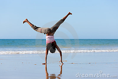 Sportive woman doing gymnastics on the beach
