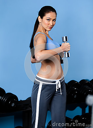 Sportive woman exercises with dumbbells