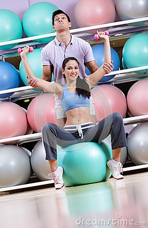 Sportive woman exercises in fitness gym